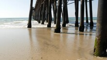Wooden Piles Under Boardwalk, Old Pier In Oceanside, California Coast USA. Pilings, Pylons Or Pillars Below Retro Vintage Bridge, Waterfront Promenade. Ocean Waves, Sea Water Tide And Sand Beach.