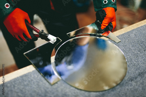 Canvas Glazier worker cutting glass with compass glass cutter in a workshop