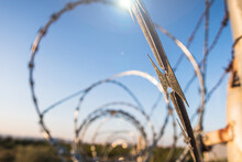 Barbed Wire With Spiral Blades, To Protect A Private Property Outside, With The Light Of The Sunset And A Natural Landscape.