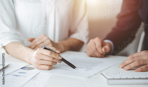 Unknown businessman and woman discussing contract in sunny office, close-up.Business people or lawyers working together at meeting