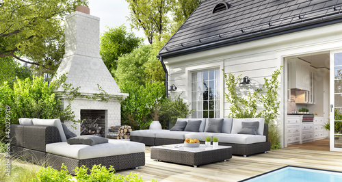 Obraz Cozy patio area with garden furniture, swimming pool and outdoor fireplace - fototapety do salonu