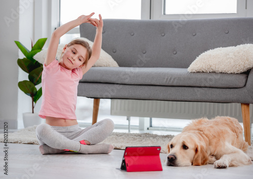 Photographie Girl exercising online with dog