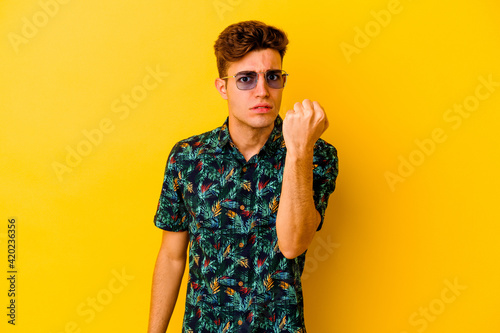 Young caucasian man wearing a Hawaiian shirt isolated on yellow background showing fist to camera, aggressive facial expression.