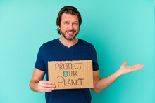 Middle Age Dutch Man Holding A Protect Our Planet Placard Isolated On Blue Background Showing A Copy Space On A Palm And Holding Another Hand On Waist.