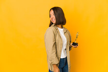 Young Hispanic Woman Holding An Award Statuette Looks Aside Smiling, Cheerful And Pleasant.