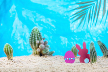 Easter Egg And Rabbit Made Of Colored Paper On The Sand With Cacti And Palm Tree Branch. Easter In The Tropics Concept