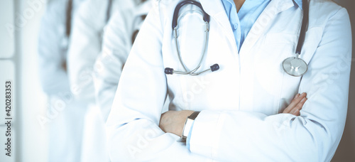 Group of modern doctors standing as a team with arms crossed in hospital office. Medical help, insurance in health care, best desease treatment and medicine concept
