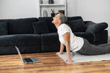 A Mature Woman Watching Yoga Classes For Senior On The Laptop, Repeats Exercises, An Elderly Female Doing Workout At Home, Leads A Healthy And Active Lifestyle
