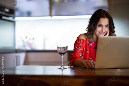 Fotografija Pretty, mid-aged woman having a virtual Wine Tasting Dinner Event Online Using L