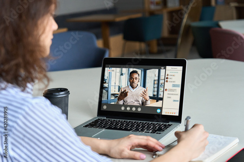 Teen girl student watching webinar, distance learning on video call with african online teacher or virtual tutor studying university seminar having online meeting on laptop screen. Over shoulder view