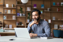 Smiling Bearded Indian Businessman Working On Laptop In Modern Office Lobby Space. Young Indian Student Using Computer Remote Studying, Watching Online Webinar, Virtual Training On Video Call Meeting.