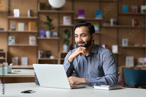 Smiling bearded indian businessman working on laptop in modern office lobby space Poster Mural XXL