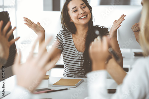 Group of business people discussing questions at meeting. Headshot of casual dressed businesswoman happy smiling to her colleague at office negotiation. Teamwork and cooperation in corporate