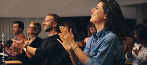 Tela Business professionals applauding at a seminar