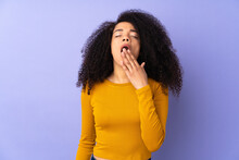 Young African American Woman Isolated On Purple Background Yawning And Covering Wide Open Mouth With Hand