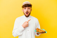 Young Moroccan Man Wearing The Typical Arabic Costume Eating Arabian Sweets Isolated On Yellow Background Pointing To The Side