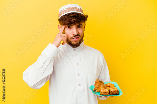 Young Moroccan man wearing the typical arabic costume eating Arabian sweets isolated on yellow background showing a disappointment gesture with forefinger Fototapet