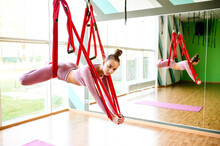 Aerial Yoga In Hammock. Slim Athletic Woman Performs Gravity Fly Yoga And Stretching Exercises. Yoga Class With A Large Mirror