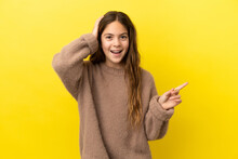 Little Caucasian Girl Isolated On Yellow Background Surprised And Pointing Finger To The Side