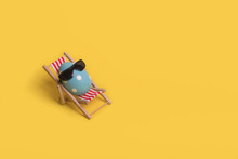 Creative Funny Idea With Easter Egg With Sunglasses While Sitting On Deck Chair On Illuminating Yellow Background.