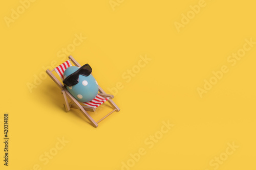 Fototapeta Creative funny idea with Easter egg with sunglasses while sitting on deck chair on illuminating yellow background
