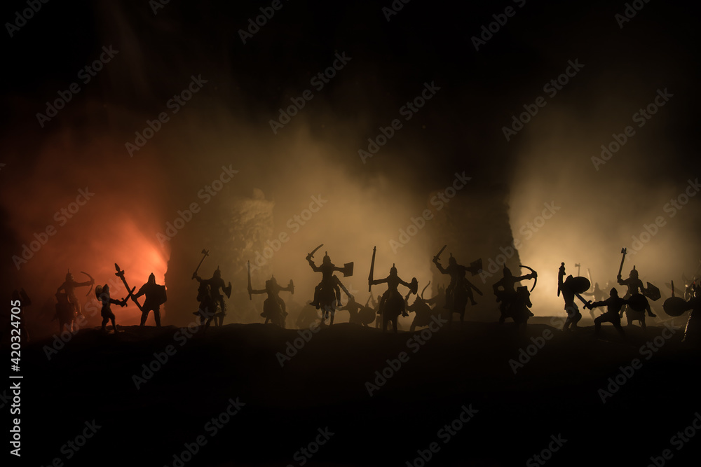 Fototapeta Medieval battle scene. Silhouettes of figures as separate objects, fight between warriors at night. Creative artwork decoration. Foggy background.