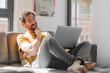 young bearded man smiling with a happy, confident expression with hand on chin, wondering and looking to the side with a laptop on a couch laptop concept