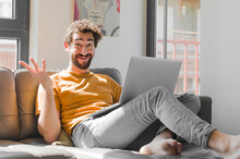 Young Bearded Man Feeling Happy, Surprised And Cheerful, Smiling With Positive Attitude, Realizing A Solution Or Idea With A Laptop On A Couch Laptop Concept