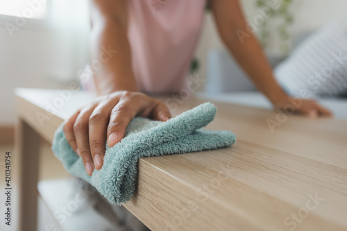 Slika na platnu Woman cleaning and wiping the table with microfiber cloth in the living room