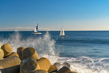 Beautiful Ocean View With Waves And Sailboats In The Background.