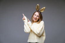 Young Beautiful Woman In Golden Rabbit Ears Shows Tongue And Finger To The Side On Gray Background