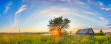 Panoramic View On Sunset Over Old Wooden Hut And Lonely Tree In Countryside