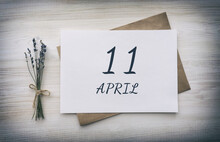 April 11. 11th Day Of The Month, Calendar Date.White Blank Of Paper With A Brown Envelope, Dry Bouquet Of Lavender Flowers On A Wooden Background. Spring Month, Day Of The Year Concept