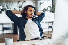 Young Businessman Sitting In Office With Hands Behind His Head Satisfied With Work Done