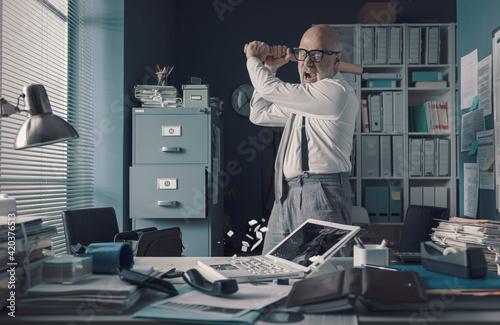 Fototapeta Crazy businessman destryoing his office with a baseball bat