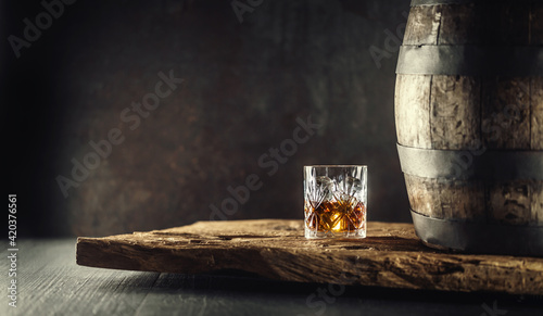 Photographie Glass of whisky or bourbon in ornamental glass next to a vinatge wooden barrel o