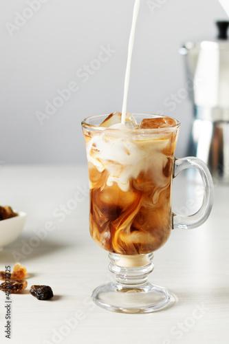 Fototapeta Pouring milk into glass with iced coffee. obraz