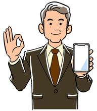 スマートフォンを手に持ちOKのサインを出す管理職男性