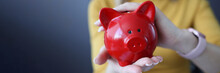 Woman Holding Red Piggy Bank In Her Hands Closeup