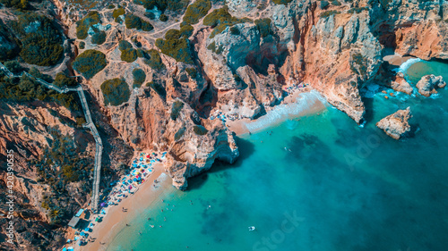 Fotografie, Tablou Aerial view of a stunning sandy beach with foamy waves and colorful sunbeds in A