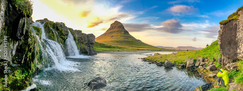 KIRKJUFELL, ICELAND - AUGUST 8, 2019: Kirkjufellfoss scenic spot with iconic waterfall and peak