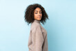 Young African American woman isolated on blue background . Portrait