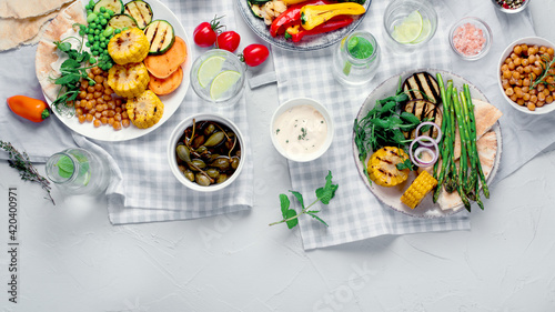 Photo Delicious grilled vegetables with sauces and snacks served on light gray background
