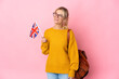 Leinwandbild Motiv Young Russian woman holding an United Kingdom flag isolated on pink background looking to the side and smiling