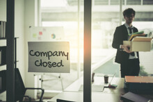 Company Closed On Windows Of An Empty Office With Business Man Packing Beloning Walking Out Of Business By Economic Recession Concept.