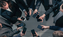 Close Up. Young Business People With Smartphones Standing In A Circle.
