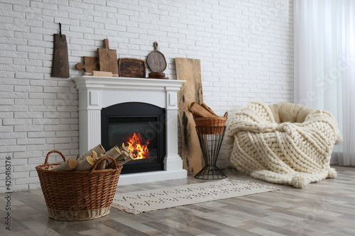 Stampa su Tela Wicker baskets with firewood and white fireplace in cozy living room