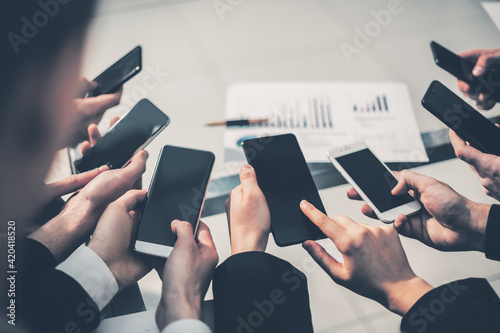group of employees using their smartphones in the workplace