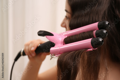 Young woman using modern curling iron against light background, focus on device Fotobehang