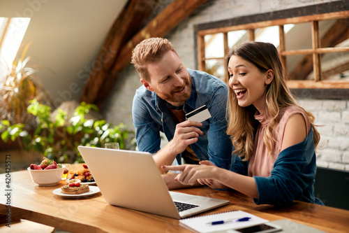 Happy couple having fun while online shopping at home.